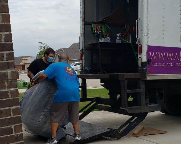 Moving guys loading and unloading furniture onto a truck