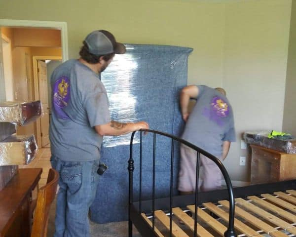 Two moving guys packing a bedroom in Temple TX